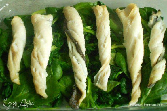 Переложить шпинат в смазанную сливочным маслом огнеупорную форму, слегка посолить, сверху поместить рыбу и поставить под выключенный гриль, чтобы блюдо было в тепле.