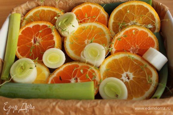 Апельсин, мандарины и порей нарезать толстыми колечками и выложить в форму, застеленную пергаментом.