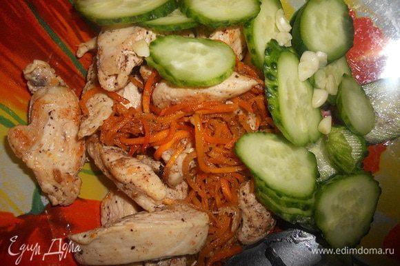 Переложить обжаренное филе в другую тарелку, добавить огурец, порезанный тонкими кружочками, и чеснок, мелко порезанный, и перемешать.