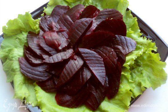 На блюдо уложить листья салата. У меня был обычный салат, но можно брать и «Айсберг» или другой салат по Вашему вкусу. Сверху выложить нарезанную тонкими ломтиками свеклу.