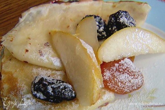 На готовые блины выложить сухофрукты с грушей и посыпать сахарной пудрой.