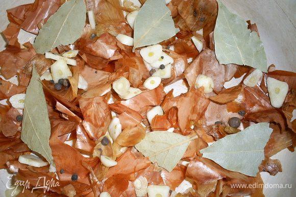 """Луковую шелуху промываем и распределяем по дну кастрюльки, в которой будут готовиться наши """"шпроты"""". Ее следует взять такую, чтоб можно было поставить в духовку. Старайтесь укрыть шелухой все дно, чтоб рыбка не прилипла. Сверху выкладываем лавровый лист, перец горошком и почищенный и нарезанный пластинками чеснок."""