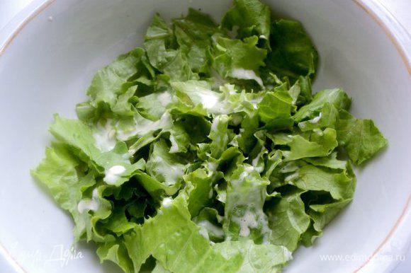 Салат предварительно помыть, обсушить и положить в холодильник. В холодном виде он более хрустящий и дольше сохраняет свежесть. Охлажденный салат порвать руками в салатник, полить немного соусом и перемешать.
