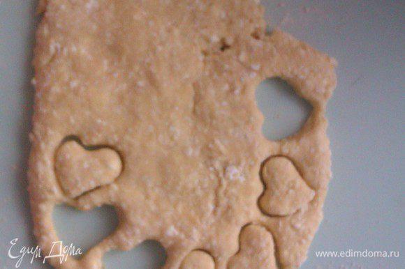 Взять небольшие формочки для печенья и вырезать фигурки из теста. Остатки теста снова размять в лепешку и вырезать фигурки. Так же поступить с остальными частями теста.