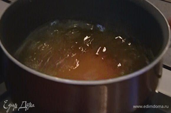 Приготовить карамель: оставшийся сахар всыпать в небольшую кастрюлю, залить 50 мл воды и на медленном огне сварить сироп, затем влить его в сковороду с кунжутом и, перемешивая, прогревать до золотистого цвета.