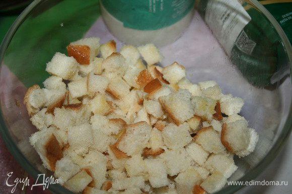 Ломтики хлеба нарезать кубиками, положить их в миску и полить растопленным сливочным маслом (50 г). Отставить в сторонку.