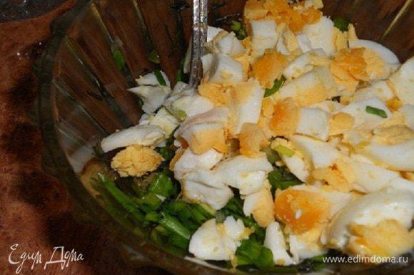 Добавить порезанные кубиками вареные яйца к зелени, посолить и поперчить, перемешать.