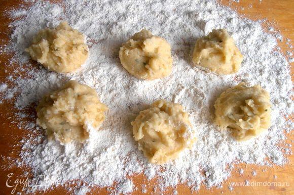 На доску густо сыплем слой муки и выкладываем при помощи двух ложек порции картофельной массы.