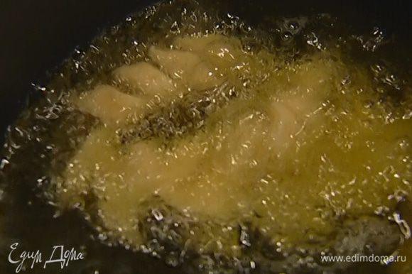 Разогреть растительное масло для фритюра и порциями пожарить в нем хворост.