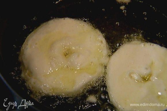 Опускать в кляр яблочные кольца и жарить их в кипящем масле до румяной корочки.
