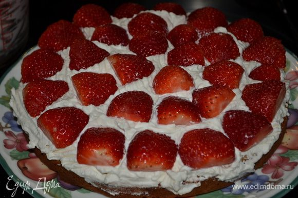 Взбить сливки с сахаром и ванилином. Выложить на бисквит распределить по нему ровно, затем клубнику.