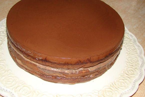 Закрепить тортовое кольцо (от разъемной формы, в которой вы выпекали торт) вокруг коржей, залить глазурью верх. Когда застынет - снять кольцо и обмазать бока