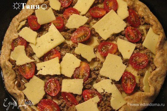 На тесто ложим кусочки сыра или натираем сыр на тёрку (У меня был сыр нарезанный тонкими пластинки поэтому я его не могла натереть и поломала на кусочки, в духовке он расплавился), посыпаем пармезаном, выкладываем слой говяжьего фарша, обжаренного с луком и часноком и любимыми специями, выкладываем снова сыр, раскладываем половинки помидорок черри, посыпаем пармезаном.