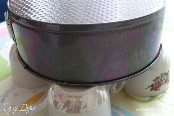 Готовый бисквит охладить в перевернутом состоянии. Для этого можно использовать решетку или взять четыре одинаковые чашки и на них положить перевернутую форму с бисквитом.