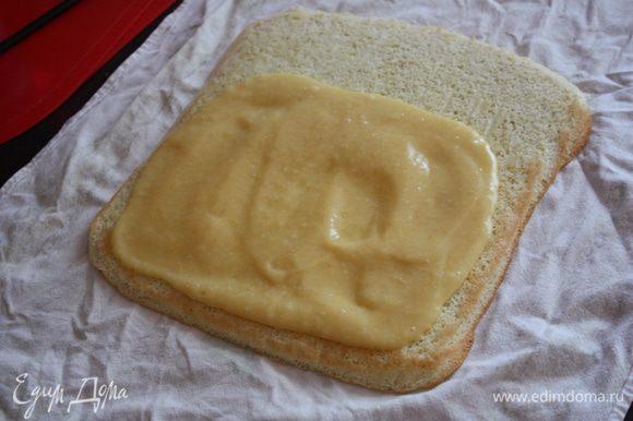 Кладем бисквит на полотенце. Наносим 2/3 крема на бисквит, оставляя небольшую полоску открытой.