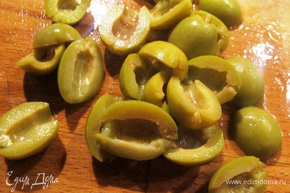 Оливки порезать напополам.