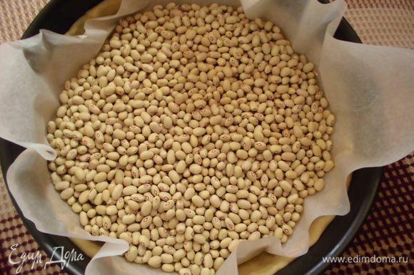 На тесто выложить бумагу для выпечки ( по размеру формы), сверху присыпать горохом или фасолью. Поставить в духовку на 20 минут.