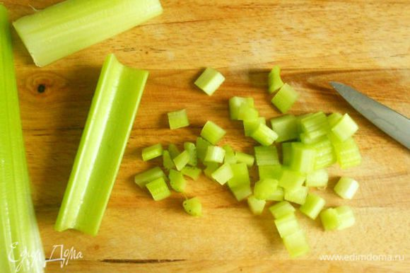 Со стеблей сельдерея (с внешней стороны) удалить волокна и нарезать мелкими кубиками. Как и редис, положить в холодную воду в другую миску.
