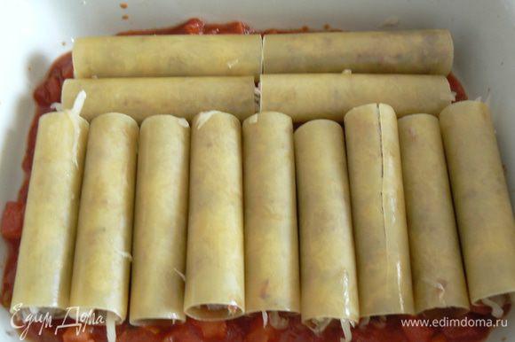 в форму для запекания поместить небольшое количество соуса, затем начиненные каннелони
