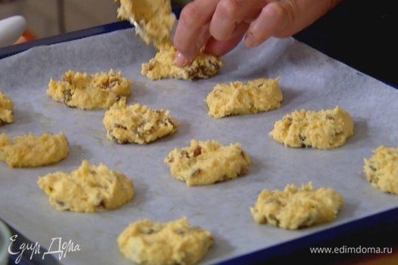 Противень выстелить бумагой для выпечки, смазать ее растительным маслом и ложкой выложить тесто в виде небольших лепешек на расстоянии 2 см друг от друга.