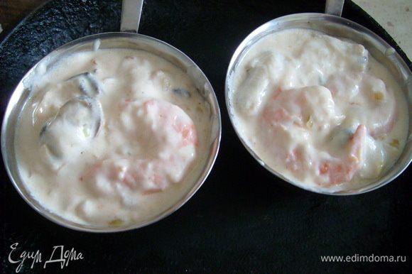 Выложить морепродукты с соусом в кокотницы, посыпать сыром и запекать в духовке 5-7 мин.