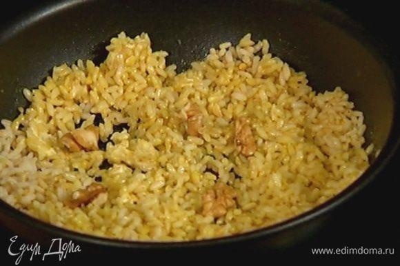 Орехи поломать руками, чтобы остались крупные кусочки, и добавить к рису.
