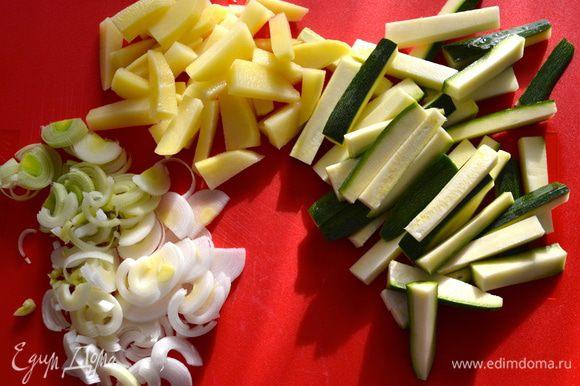 Нарезать полукольцами лук-порей (можно заменить на 2 стебля зеленого лука). Кабачок и картошку нарезать небольшими брусочками.