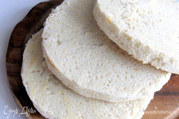 Аккуратно срезать корку с хлеба. Разрезать буханки на коржи толщиной примерно 1 см.