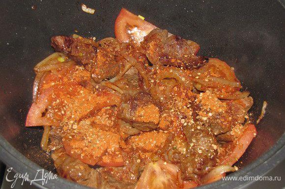 Положите помидоры. Во время их обжарки добавьте смесь специй, убавьте немного огонь. Потушите мясо с луком и помидорами, 5 минут.