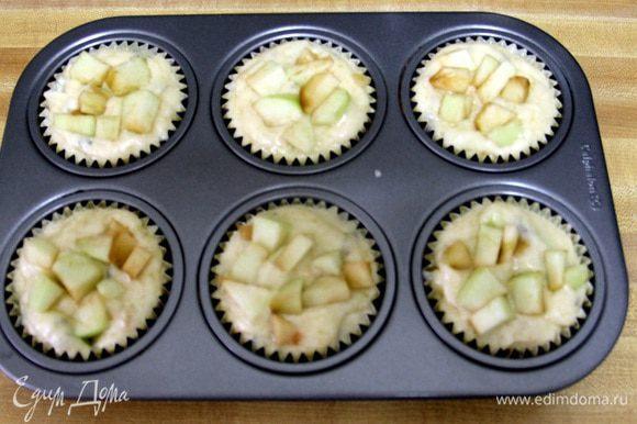 Раскладываем приготовленное тесто в формы для маффинов и сверху кладем оставшиеся яблоки.