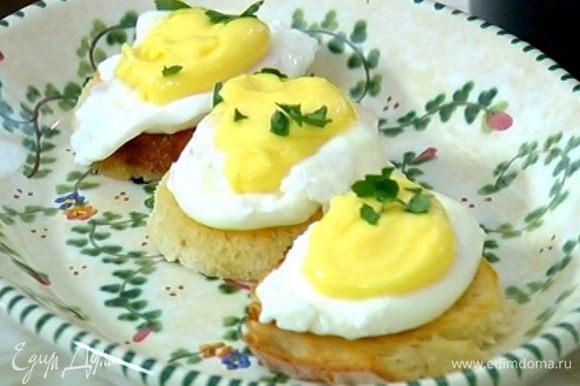 На гренки поместить яйца пашот, а сверху выложить соус. Украсить листьями петрушки.