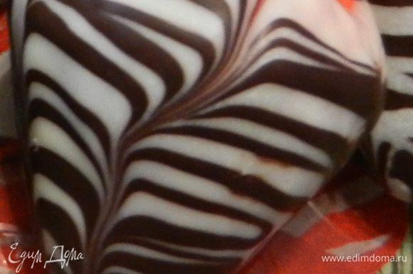 Чтобы получить такой узор, нужно после нанесения белого шоколада , охладить. Затем нанести полоски молочного шоколада и шпажкой провести полосу сверху вниз, узор смешается, как на рисунке, и потом ставить охлаждать снова.