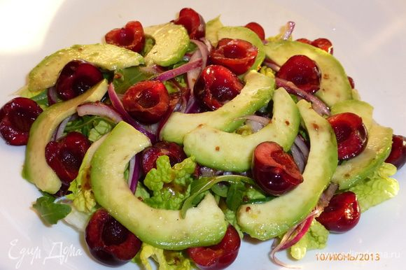 Собираем салат. На тарелку выкладываем листья салата, поливаем их заправкой. Далее лук, авокадо и черешня, поливаем заправкой.