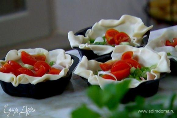 В формы выложить ветчину, зеленый лук, помидоры, посолить и поперчить, посыпать сыром (немного сыра оставить) и залить взбитыми яйцами с молоком.
