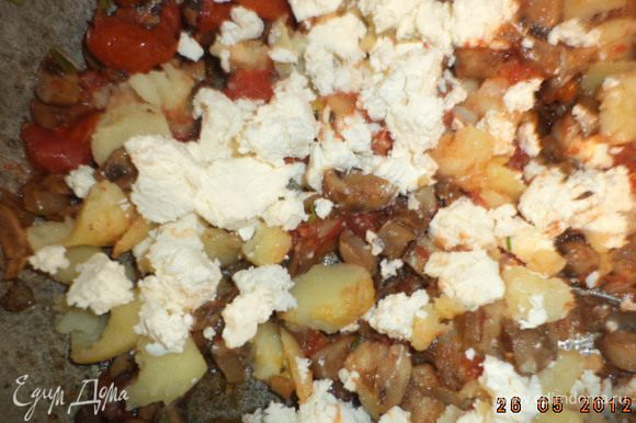 К грибам прибавить выбранную мякоть картофеля и 200 г феты. Тщательно перемешать.