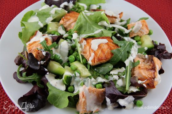 В салатнице перемешиваем салат, рукколу, огурец, горошек и раскладываем их по тарелкам. Выкладываем кусочки лосося и поливаем заправкой. Приятного аппетита)