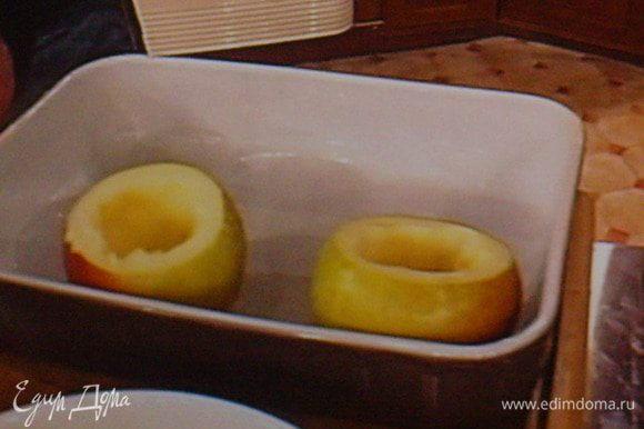 Форму для запекания обильно смазать маслом. С яблок срезать верхушку, вырезать сердцевину с мякотью.