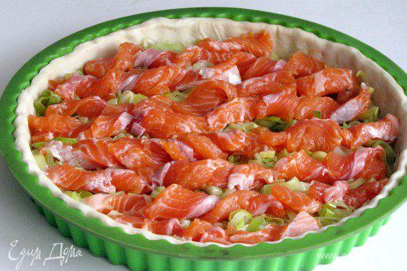 Сверху выложить филе лосося, нарезанного тонкими полосками. Полоски перекрутить.