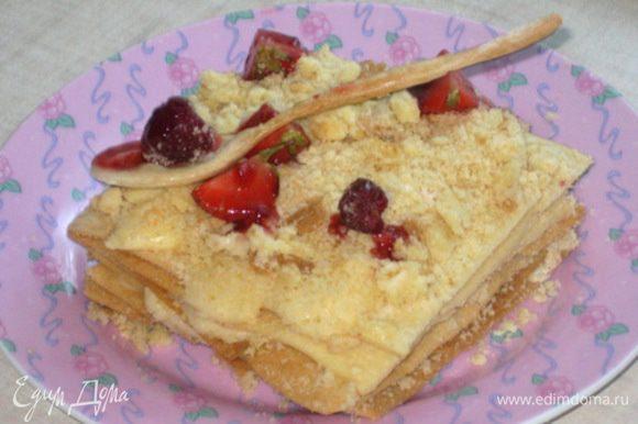 Сборка: Прослоить квадратики кремом и сверху посыпать обрезками. Украсить ложечкой и ягодами и полить джемом!