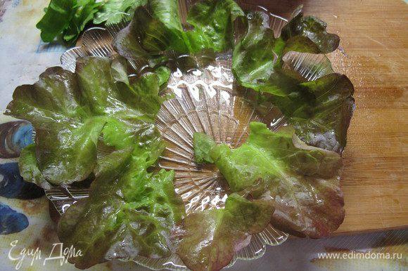 На тарелку выкладываем листья салата. Вынимаем из бульона курицу, даем ей остыть и нарезаем тонкими ломтиками.