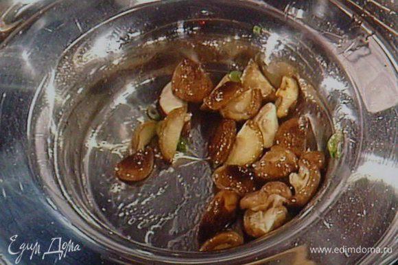 Шитаке порезать пополам, обжарить на кунжутном масле вместе с мелко нарезанным зелёным луком, отложить в сторону.