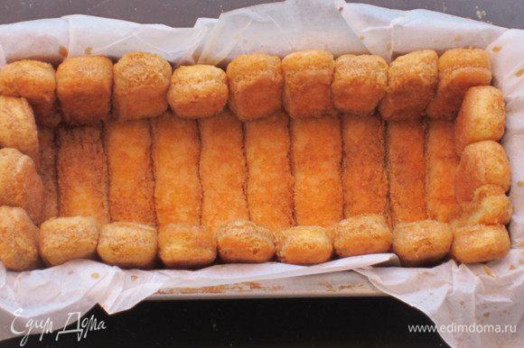 Сварить кофе, добавить ром и сахар по вкусу, пропитать печенье. Прямоугольную форму застелить пергаментом. Выложить печеньем бортик и дно формы.