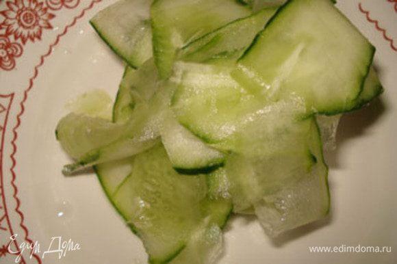 Огурец вымыть и порезать тонкими пластинками, лучше для этого использовать овощечистку.