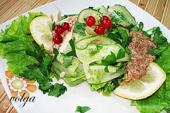 На тарелку положить листья салата, сверху полоски огурца, петрушку и тунец. Можно добавить перец. Полить лимонным соком. Украсить ягодами красной смородины.