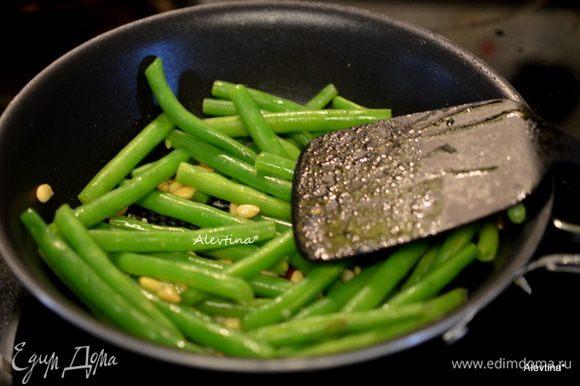 На сковороде разогреть оливковое масло, обжаривать чеснок 1 мин, затем добавить кедровые орешки 3 мин. Воду слить с зеленой фасоли, фасоль положить в сковороду, посыпать солью и черным перцем. Обжаривать несколько минут.