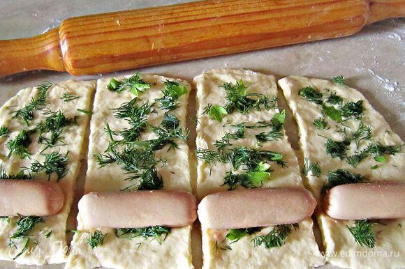 Присыпать слегка мукой стол. Раскатать тесто толщиной около 0,5 мм, нарезать полоски по длине сосисок. Каждую полоску теста посыпаем зеленью. На край укладываем сосиску и сворачиваем, формируя пирожок.