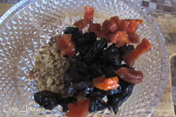 Нарежьте курагу и чернослив, раздробите орехи.