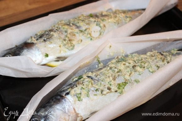 """Листы пергамента, размером чуть больше рыбы, смазать небольшим количеством масляной смеси. Уложить сверху скумбрию. Смазать рыбу сверху и в брюшке оставшимся ароматным маслом. В брюшко уложить 2 полудольки лимона. Концы пергамента соединить и скрутить, образуя """"лодочку"""" вокруг рыбы. Выпекать скумбрию около 20 минут при 180*С. Если хочется более румяной корочки, то можно на минуту поставить готовую рыбу под гриль."""