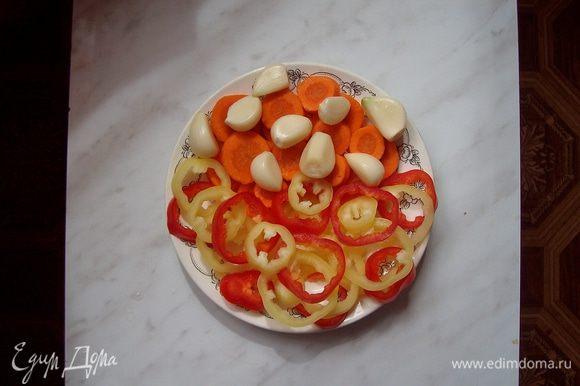 Нарезаем болгарский перец и морковь кружочками, чистим зубчики чеснока и корень хрена. Половинку корня хрена можно не нарезать, но мы нарезаем тонкими пластинками