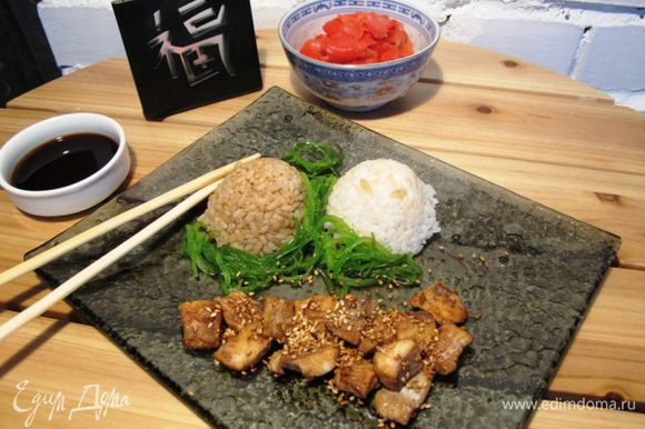 Рис делим на две части. В одну добавляем соевый соус. Сервируем на блюде белый и коричневый рис раздельно. Лосось посыпаем жареным кунжутом. Украшаем чукой и маринованным имбирем. Отдельно подаем соевый соус. Itadakimasu!